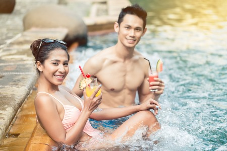 Handsome young man flirting with an attractive woman while drinking delicious cocktails in a trendy swimming pool during summer vacations Stock Photo