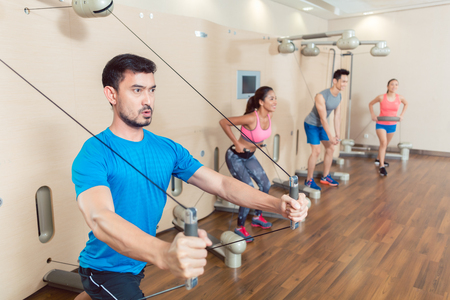 Portrait of a determined fit young man exercising with the resistance bands of an anchor gym system mounted on wall in a trendy fitness club Stock Photo