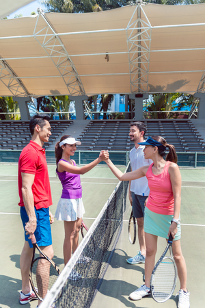 Four young and competitive tennis players putting hands together above the net as a gesture of fair play before a doubles mixed match Stok Fotoğraf