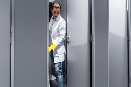 Sprzątaczka lub woźny wycierająca podłogę w toalecie sprzątająca stoisko
