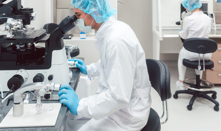 Scientist working on manipulator to fertilize human egg cells using manipulator and microscope
