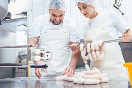 Team of butchers, woman and man, filling sausage in meat industry Banque d'images