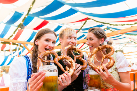 Three friends at the Regensburger Dult eat giant pretzels and drink beer in tent