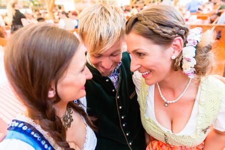 Man hugs two dirndl wearing women in a beer tent at Bavarian folk fair