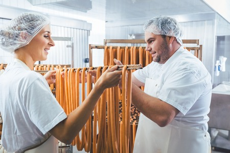 Woman working in butchery putting sausages on beam in rack for smoking Stockfoto