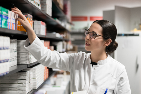 Portrait of a dedicated female pharmacist taking a medicine from the shelf, while wearing eyeglasses and lab coat during work in a modern drugstore with various pharmaceutical products
