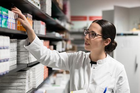 Retrato de una farmacéutica dedicada a tomar un medicamento del estante, mientras usa anteojos y bata de laboratorio durante el trabajo en una farmacia moderna con diversos productos farmacéuticos Foto de archivo