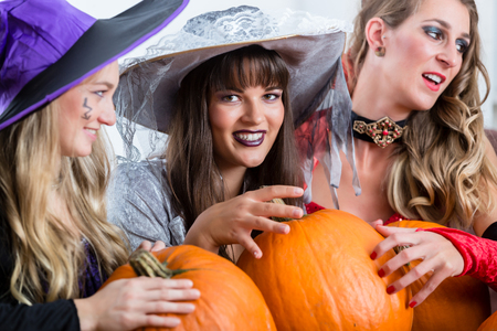 Three young and beautiful women wearing funny party costumes while acting as witches joining their malicious forces at Halloween Stock Photo
