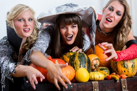Four cheerful beautiful women toasting while celebrating Halloween together during costume party indoors in a decorated room