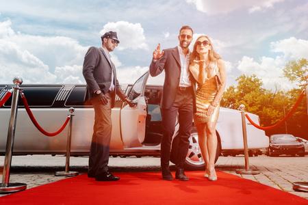 Coppia in arrivo con la limousine che cammina sul tappeto rosso, un autista sta aprendo la portiera della macchina