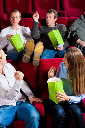 Group of people eating popcorn while man keeping legs on chair disturbing couple sitting in audience Stock Photo