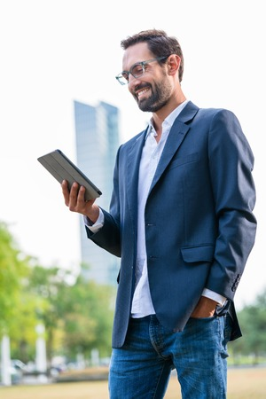 Close-up of stylish businessman with hand in the pocket looking at digital tablet 版權商用圖片