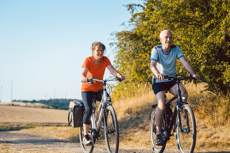 Senior couple riding their bicycles for better fitness and health benefits Stock Photo