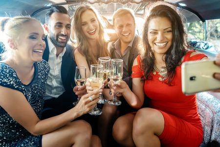 Party-Leute in einer Limousine mit Getränken, die ein Selfie mit Telefon nehmen, das in die Kamera lächelt Standard-Bild