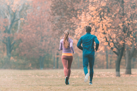Fall running in a park, seen from behind couple of man and woman