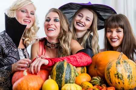 Vier fröhliche schöne Frauen, die anstoßen, während sie Halloween zusammen während der Kostümparty drinnen in einem dekorierten Raum feiern