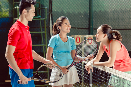Three young cheerful players and friends smiling while talking before playing together doubles match on a professional tennis court