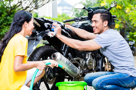 Close-up of happy young couple washing motorcycle at outdoors