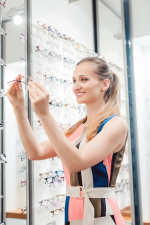 Beautiful woman choosing new glasses in store being yet undecided Stock Photo