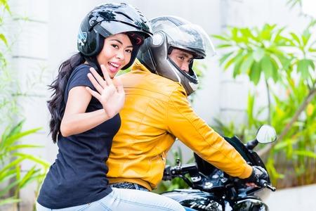 Girlfriend waving her hand sitting with his boyfriend on motorbike 写真素材