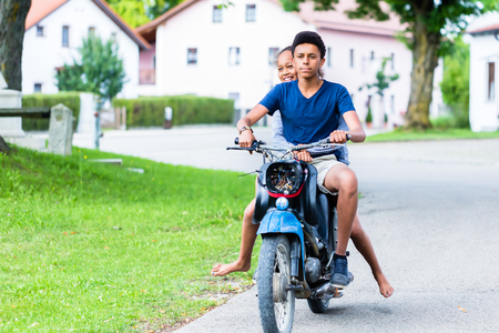 Happy brother and sister enjoying the ride on motorbike Stockfoto