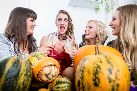 Young and beautiful woman posing funny and scary while toasting with her best friends during Halloween costume party Stock Photo