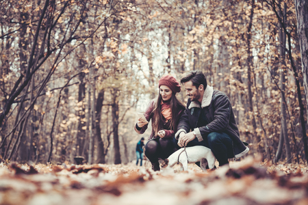 Couple in fall having walk with dog in a park playing with the pet