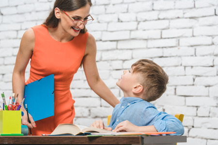 Mother helping her son to do the school homework assignment