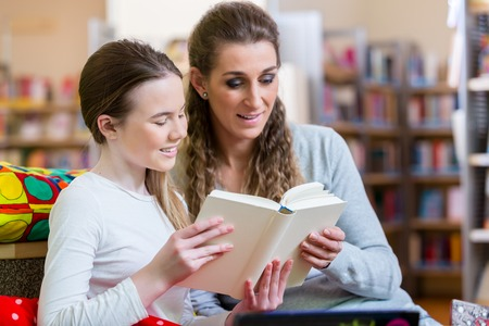 Mother and daughter reading a book in community center library with fun Stock Photo