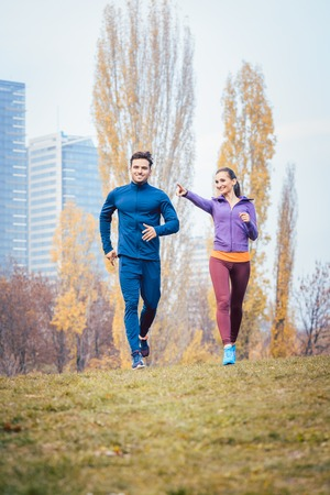 Urban jogging - couple running in autumn city on a hill