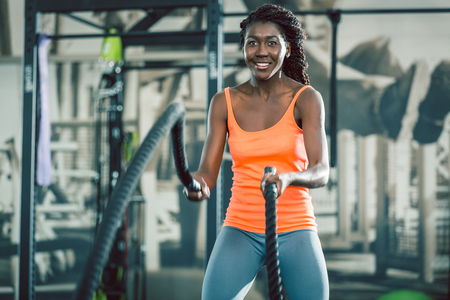 Low-angle view of a strong and beautiful African American woman, exercising alternative waves with battle ropes during high-intensity functional training workout at the gym