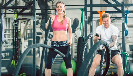 Low-angle view of two beautiful and strong women smiling while waving heavy battle ropes during functional training workout at the gym