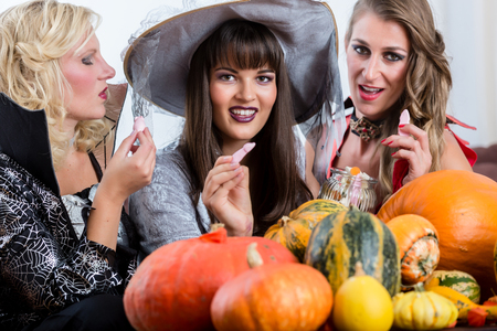 Funny young women and best friends sharing various delicious candies while celebrating Halloween together at costume party indoors