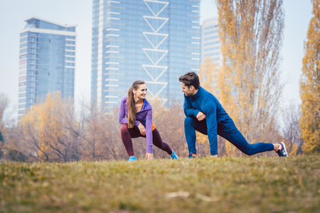 Sport couple doing warm-up exercise before starting a run to become more fit
