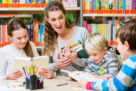 Teacher with her class visiting the library reading books for education Stock Photo