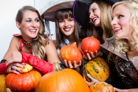 Four young and beautiful women wearing funny party costumes while acting as witches joining their malicious forces at Halloween