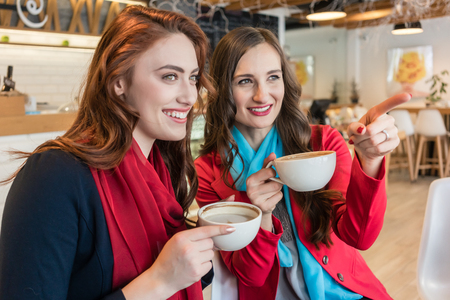 Low-angle view of two young and beautiful women daydreaming while drinking together delicious hot chocolate in a trendy coffee shop Stock Photo