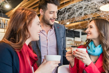 Attractive young woman meeting an old friend while sitting and enjoying a hot drink together with her best friend in a trendy coffee shop Stock Photo