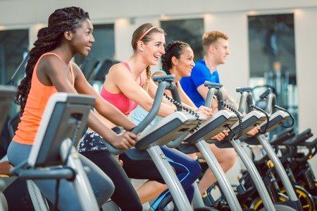 brunette beautiful woman smiling while cycling on a modern fitness bicycle during group spinning class at the gym Stock Photo