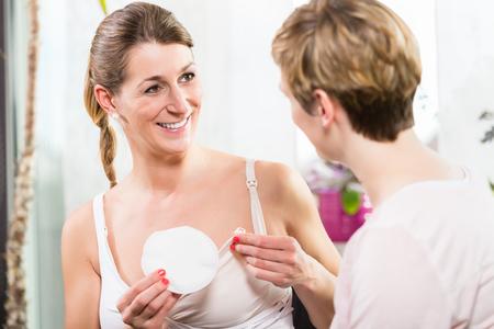 Frau, die bequeme Plastikschalen im BH verwendet, um überschüssige Milch zu sammeln Standard-Bild