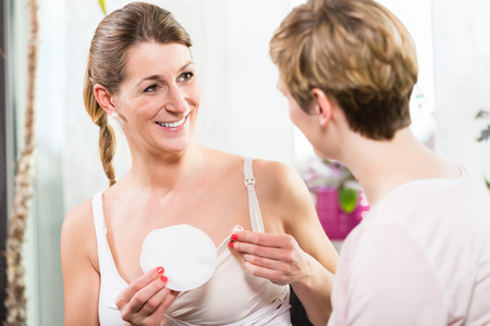 Woman using comfortable plastic shells inside bra for collecting excess milk Stock fotó