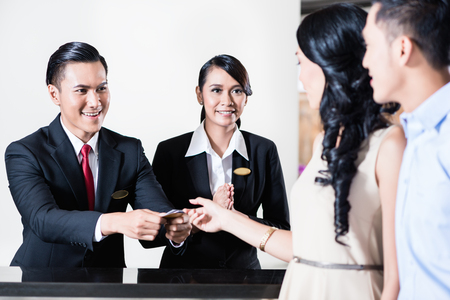 Happy employees are welcoming young couple guest in hotel