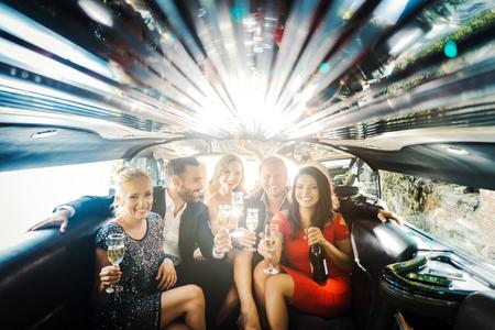 Feier in einer Limousine, Frau und Männer trinken Champagner und feiern