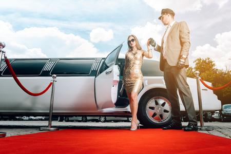 Conductor ayudando a mujer VIP o estrella fuera de limusina en la alfombra roja a una recepción Foto de archivo