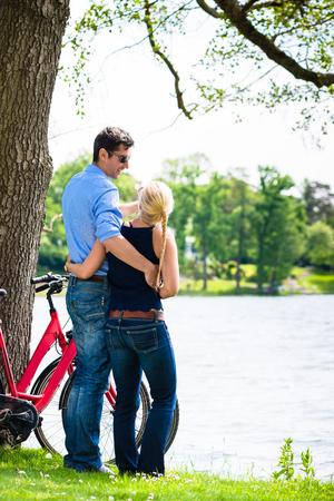 Rear view of young couple standing near the lake with bicycle Stock Photo