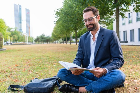 Smiling businessman sitting on lawn reading book in the park Stock Photo