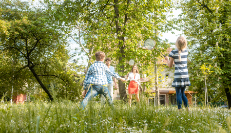 Family playing badminton on a meadow in summer having fun enjoying themselves