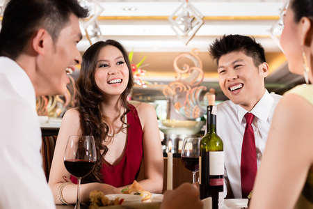 Two smiling couple enjoying in party drinking wine