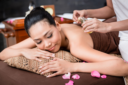 Woman receiving back massage on spa massage table