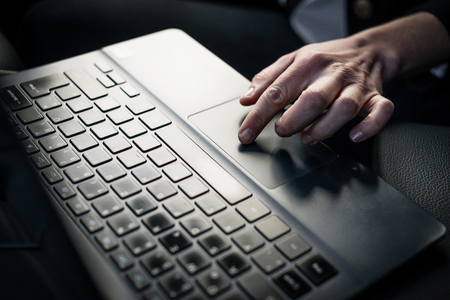 Close-up of businesswoman using laptop keypad